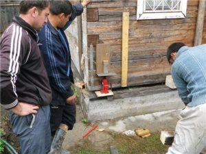 Процесс подъема дома с помощью домкрата